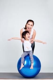 Joven madre con hija pequeña ejercicio en pelota fitness