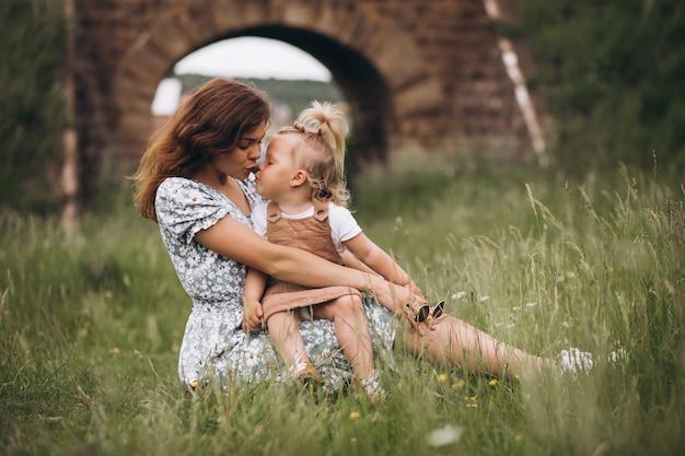 Joven madre con hija pequeña en el parque sentado en el césped
