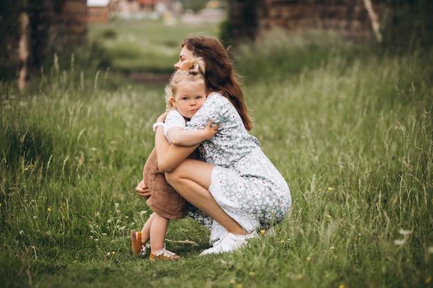 Joven madre con hija pequeña en el parque