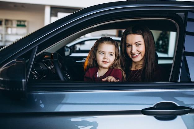 Joven madre con hija pequeña sentada dentro de un automóvil