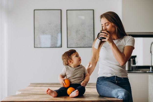 Joven madre con hijo pequeño bebiendo agua en casa