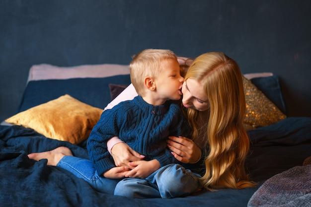 Una joven madre con un hijo pequeño sentado en la cama en un abrazo
