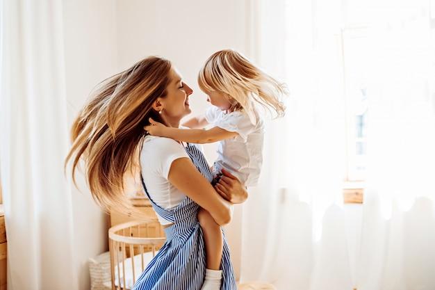 Joven madre jugando con niño pequeño en casa