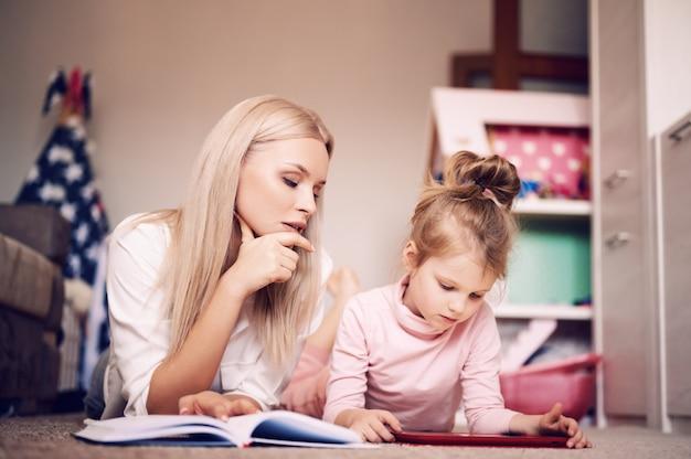 Joven madre lee un libro en casa tirado en el piso en casa con su hija