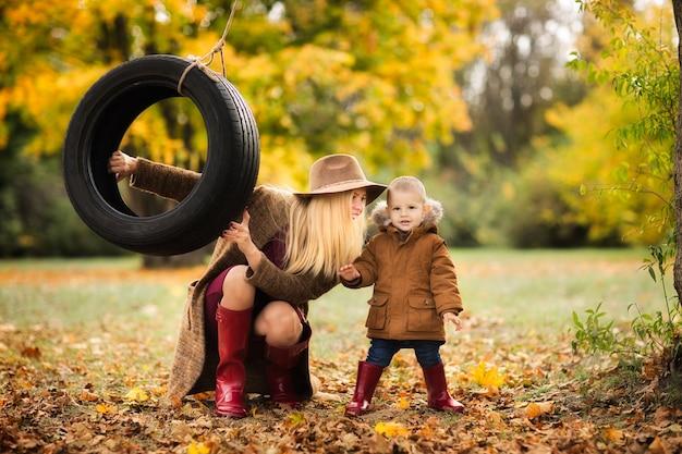 Joven madre monta a los niños en una rueda en el parque de otoño