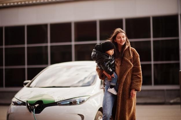 Joven madre con niño carga electro coche en la gasolinera eléctrica.