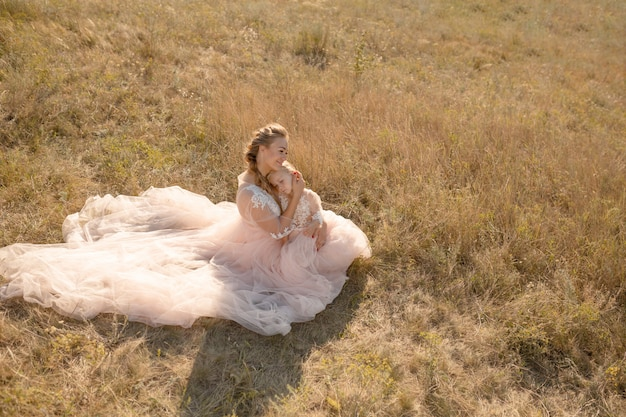 Joven madre con una pequeña hija en vestidos rosados están sentados en el campo. mamá abraza a su hija y la abraza