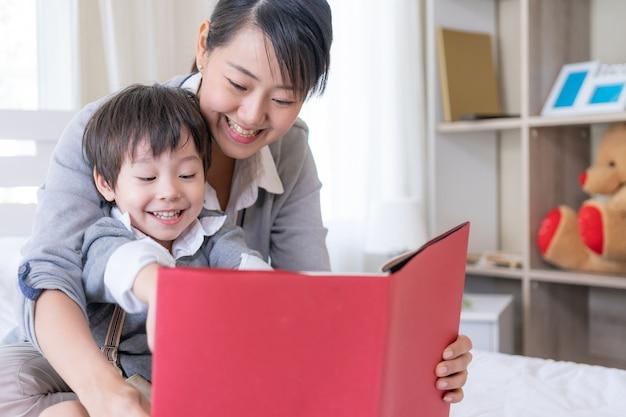 Joven madre y pequeño hijo leyendo libro en casa