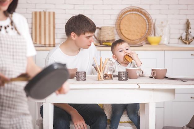 Joven madre de pie delante de su familia en la cocina. familia feliz cenando o desayunando. mujer preparando la cena para su marido y su pequeño bebé.