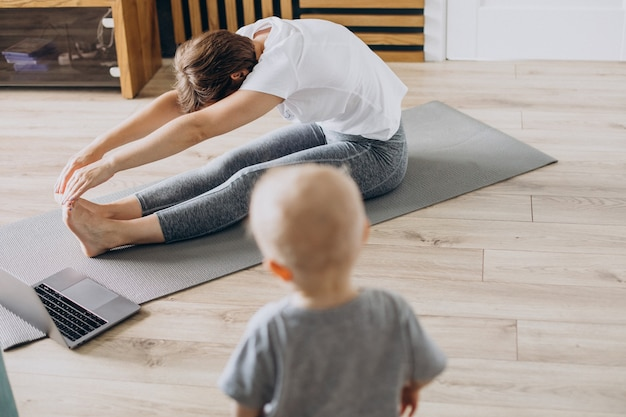 Joven madre practica yoga con su hijo pequeño en la estera