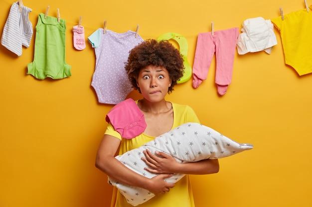 Joven madre preocupada se muerde los labios y mira con sorpresa, posa con el bebé en las manos, intenta adormecer al recién nacido que llora todo el tiempo, se muerde los labios nerviosamente, no tiene experiencia de la maternidad