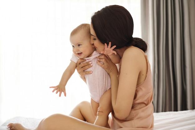 Joven madre en ropa de dormir sonriendo abrazando besando a su bebé sentado en la cama sobre la ventana. ojos cerrados.