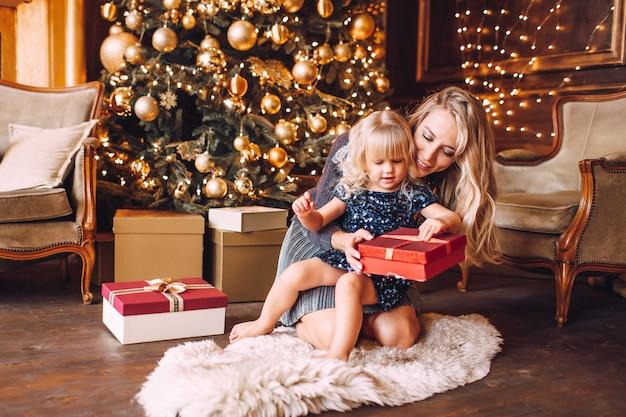 Joven madre rubia y su pequeña hija en ropa brillante abriendo un regalo de navidad cerca de un árbol de navidad en la acogedora sala de estar en invierno