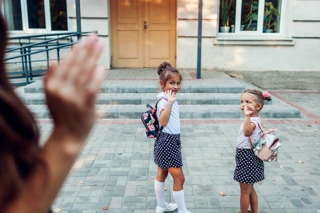 Joven madre saludando a sus hijas antes de las clases en la escuela primaria al aire libre despidiéndolas.