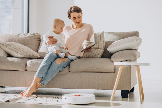Joven madre sentada en un sofá con un hijo pequeño y viendo robot aspirador haciendo las tareas del hogar