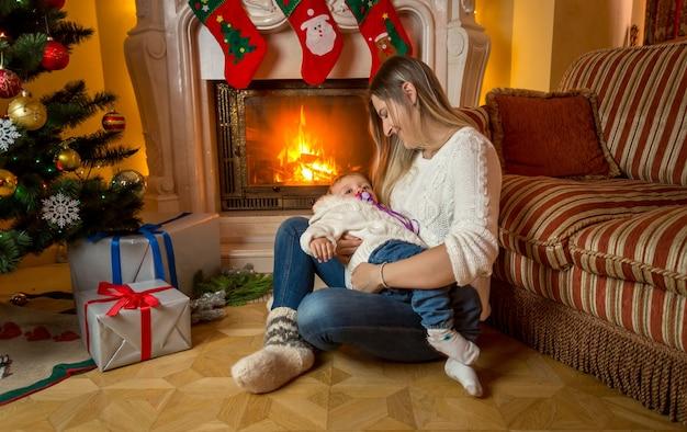 Joven madre solícita sentada con su bebé en la chimenea en la víspera de navidad