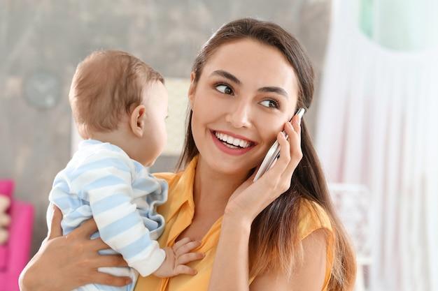 Joven madre sosteniendo bebé mientras habla por teléfono en casa
