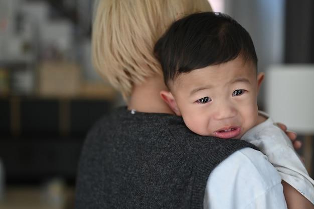 Joven madre sosteniendo a su hijo llorando en casa.