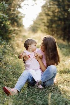 Joven madre con su adorable bebé en el bosque