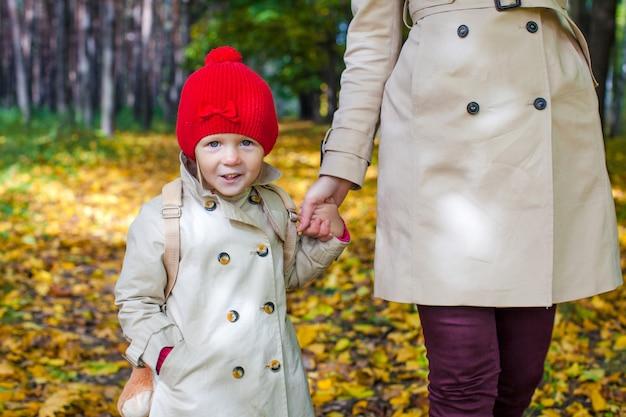 Joven madre y su adorable hija caminando en el bosque amarillo del otoño en un cálido día soleado