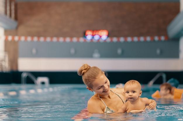 Joven madre y su bebé disfrutando de una lección de natación para bebés en la piscina. niño divirtiéndose en el agua con mamá