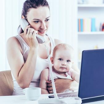 La joven madre y su bebé usando una computadora portátil para comunicarse con la abuela a través de skype, en casa en la guardería