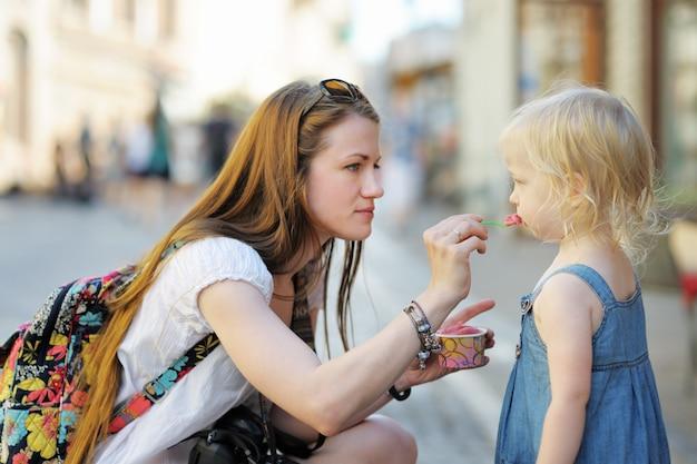 Joven madre y su hija comiendo helado al aire libre