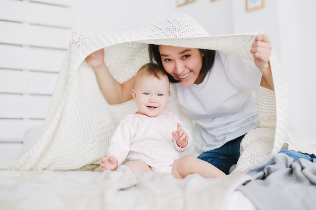 Joven madre con su hija juegan a las escondidas en el dormitorio