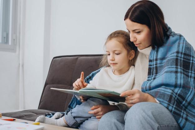 Joven madre con su hija leyendo un libro envuelto en tela escocesa.