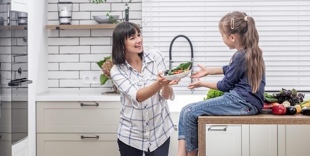 Joven madre con su hija con muchas verduras en el fondo del interior de una cocina ligera moderna.