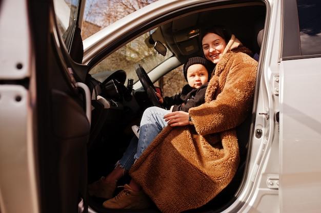 Joven madre y su hijo en el coche. concepto de conducción segura.