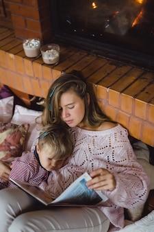 Una joven madre y su hijo están leyendo un libro de cuento de hadas cerca de la chimenea.