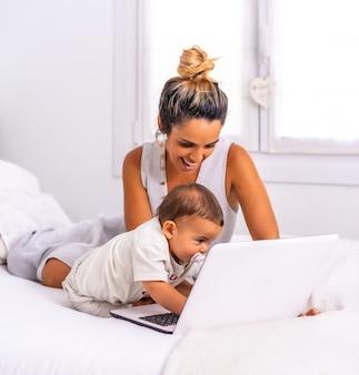Joven madre con su hijo en la habitación de la cama teletrabajando y cuidando a su hijo