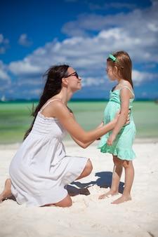 Joven madre y su linda hija se divierten en playa exótica