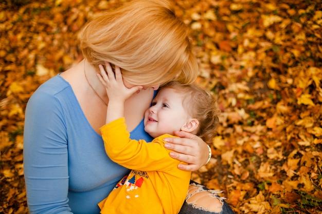 Joven madre y su niña pequeña se divierten en otoño