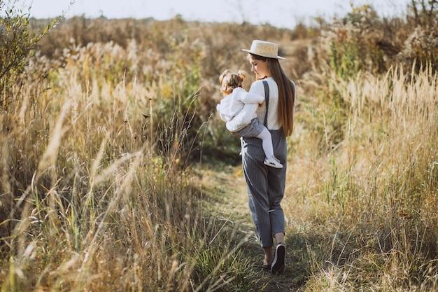 Joven madre con su pequeña hija en un campo de otoño