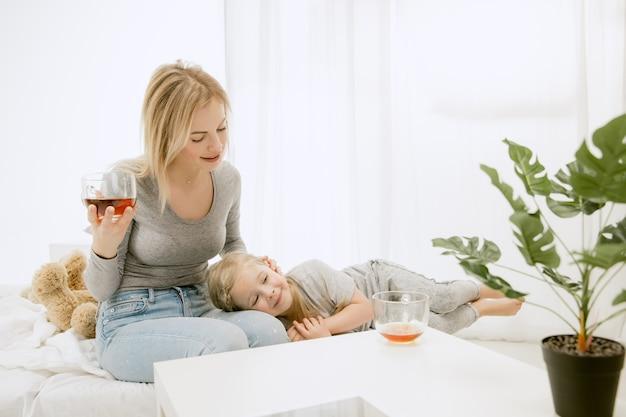 Joven madre y su pequeña hija en casa en la mañana soleada. colores pastel suaves. tiempo en familia feliz el fin de semana. concepto del día de la madre. conceptos de familia, amor, estilo de vida, maternidad y momentos tiernos.