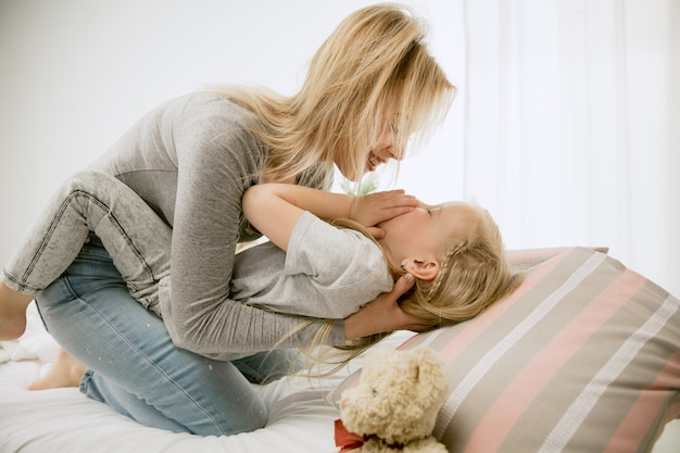 Joven madre y su pequeña hija en casa por la mañana soleada. colores pastel suaves. tiempo en familia feliz el fin de semana. concepto del día de la madre. conceptos de familia, amor, estilo de vida, maternidad y momentos tiernos.