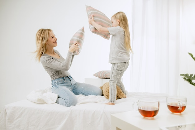 Joven madre y su pequeña hija en casa en la mañana soleada. colores pastel suaves. tiempo en familia feliz el fin de semana.