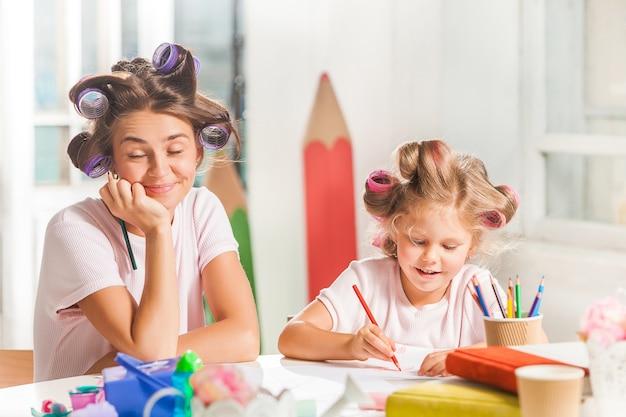 La joven madre y su pequeña hija dibujando con lápices en casa