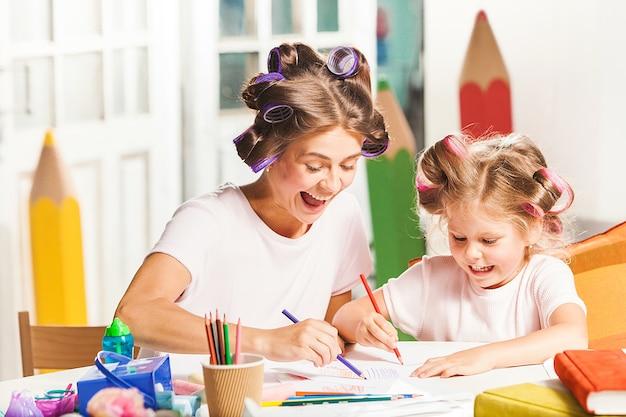 Joven madre y su pequeña hija dibujando con lápices en casa