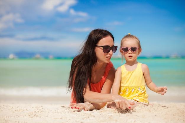 Joven madre y su pequeña hija disfrutando de las vacaciones de verano