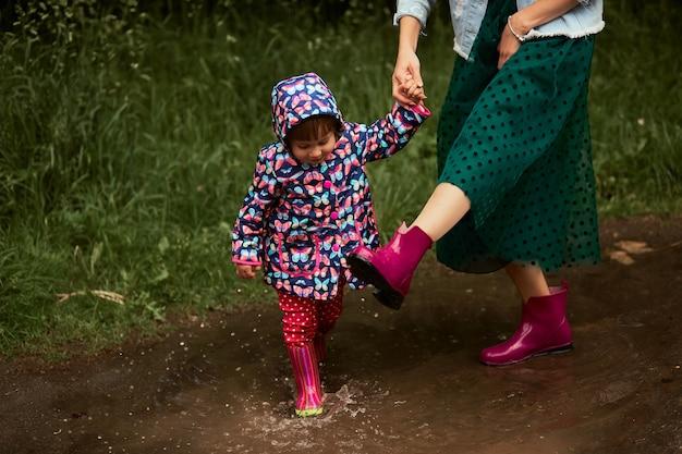 Joven madre y su pequeña hija se divierten caminando en botas de goma en las piscinas en el parque