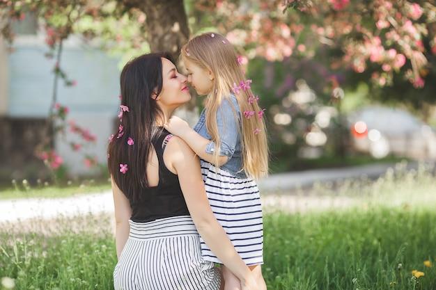 Joven madre y su pequeña hija divirtiéndose juntos al aire libre