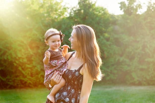 Joven madre y su pequeña hija jugando sobre césped