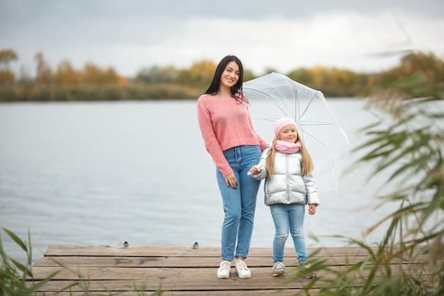 Joven madre con su pequeña hija en el otoño cerca del lago