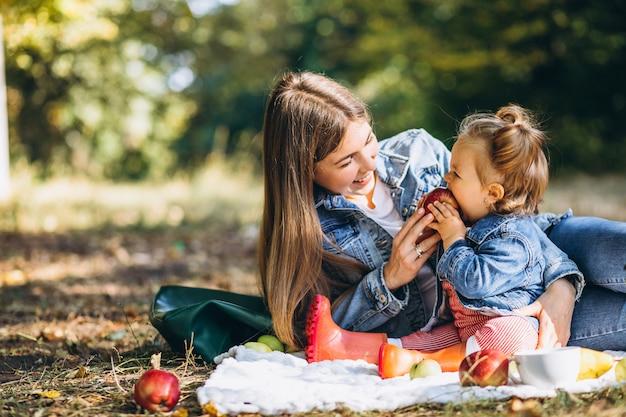 Joven madre con su pequeña hija en un parque de otoño con picnic
