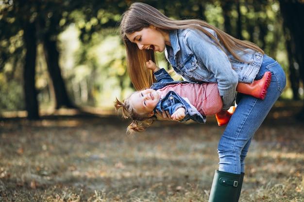 Joven madre con su pequeña hija en un parque de otoño