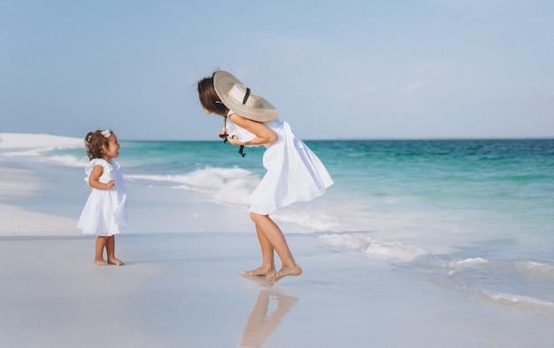 Joven madre con su pequeña hija en la playa junto al mar