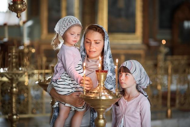 Joven madre y su pequeña hija rubia caucásica con velas en la iglesia ortodoxa rusa